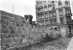 An East Berlin policeman puts bricks in place as the Berlin Wall is heightened to 15 feet, 5 m, separating East and West Berlin, Germany, on Sept. 9, 1961.  People watch from their apartment building windows in background above. (AP Photo)